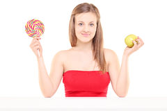 Pretty young girl holding a lollipop and an apple Royalty Free Stock Images