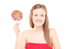 Pretty young girl holding a lollipop and looking at camera Stock Photography