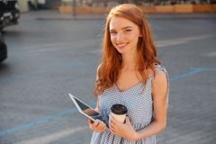 Pretty young girl holding pc tablet and cup of coffee Royalty Free Stock Images