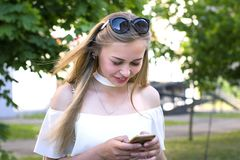Pretty girl with phone in the hand outside stock photo