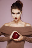 Pretty young girl holding red apple in hands looking at camera brutally. Royalty Free Stock Image