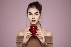 Pretty young girl holding red apple in hands looking at camera. Copy space. Stock Images