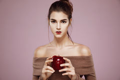 Pretty young girl holding red apple in hands looking at camera. Copy space. Stock Photo