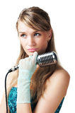 Pretty young girl holding retro microphone. Looking up, isolated on white Stock Image