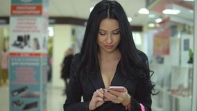 Pretty young girl is holding shopping bags and using a smart phone in mall. Pretty young girl is holding shopping bags and using a smart phone in mall stock video