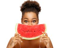 Pretty young girl holding slice of watermelon in front of her face. stock image