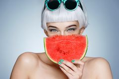 Pretty young girl holding slice of watermelon in front of her face stock images