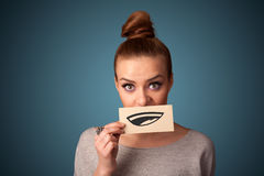 Pretty young girl holding white card with smile drawing Royalty Free Stock Photos