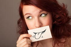 Pretty young girl holding white card with smile drawing Royalty Free Stock Photography