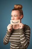 Pretty young girl holding white card with smile drawing Royalty Free Stock Images