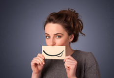 Pretty young girl holding white card with smile drawing Stock Images