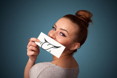Pretty young girl holding white card with smile drawing Royalty Free Stock Photo