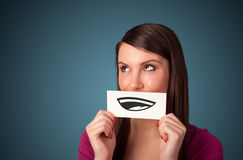 Pretty young girl holding white card with smile drawing. On gradient background Stock Images