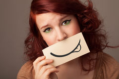 Pretty young girl holding white card with smile drawing. On gradient background Stock Photos