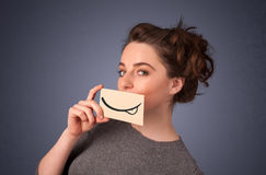 Pretty young girl holding white card with smile drawing. On gradient background Royalty Free Stock Photos