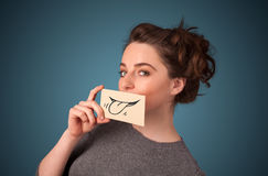 Pretty young girl holding white card with smile drawing. On gradient background Stock Photo