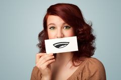 Pretty young girl holding white card with smile drawing. On gradient background Royalty Free Stock Photo