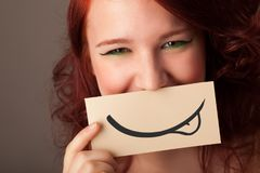 Pretty young girl holding white card with smile drawing. On gradient background Stock Photography