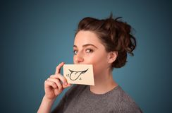 Pretty young girl holding white card with smile drawing. On gradient background Stock Image
