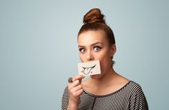 Pretty young girl holding white card with smile drawing. On gradient background Royalty Free Stock Image