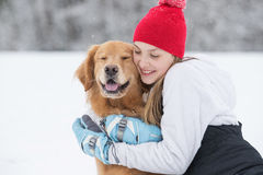 Pretty young girl hugging her golden retriever dog in the snow Royalty Free Stock Photos