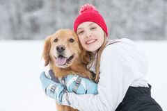 Pretty young girl hugging her golden retriever dog in the snow Stock Image