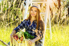 Pretty and young girl keeping wooden box full of vegetables. Summer harvest. Royalty Free Stock Photos