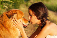 Pretty young girl kisses her cute dog Royalty Free Stock Photo