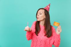 Pretty young girl in knitted pink sweater, birthday hat with closed eyes blowing out candle on cake, hold in hand credit. Card isolated on blue background stock image
