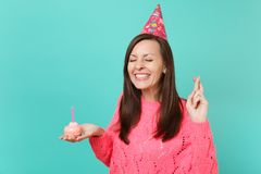 Pretty young girl in knitted pink sweater birthday hat keeping fingers crossed eyes closed hold in hand cake with candle. Isolated on blue wall background royalty free stock photos