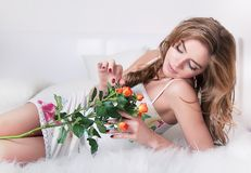 Pretty young girl laying in bed with roses Royalty Free Stock Photos