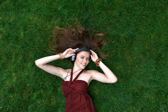 Pretty young girl listen music in headphones lying on grass. Pretty young girl portrait, listening music in headphones lying on grass in park, happy and smiling Royalty Free Stock Photography