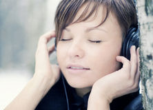 Pretty young girl listening music. Outdoor Stock Images