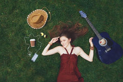 Pretty young girl listening music in earphones lying on grass Stock Photography