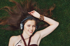 Pretty young girl listening music in headphones lying on grass Royalty Free Stock Photography