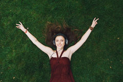 Pretty young girl listening music in headphones lying on grass Stock Photography