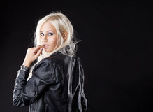 Pretty young girl look at camera with desire. Pretty young blond girl look at camera with desire in leather Stock Photos