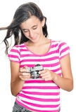 Pretty young girl looking at images on a compact camera Royalty Free Stock Image