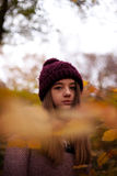 Pretty young girl looking through leaves. Pretty young girl looking Autumnal through leaves in a forest Royalty Free Stock Image