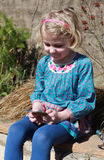 Pretty young girl looking at a packet of seeds Royalty Free Stock Photo