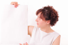 Pretty young girl looks at a big piece of paper Stock Images