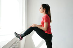 Pretty young girl looks out the window and does warming exercises and stretching before training. Single sports and Royalty Free Stock Photography