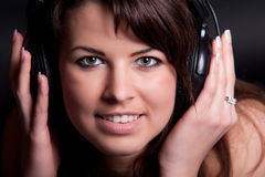 Pretty young girl loves her music and is feeling t. A beautiful young girl listens to music on headphones at studio stock photography