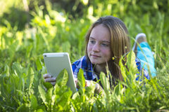 Pretty young girl lying in the grass at park with a tablet. Outdoors. Stock Photos