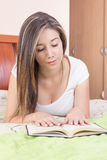 Pretty young girl lying on her stomach reading a Stock Photos