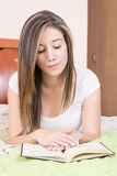 Pretty young girl lying on her stomach reading a Stock Image