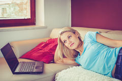 Pretty Young Girl Is Lying on a Sofa by Her Laptop Royalty Free Stock Photos