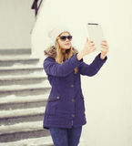 Pretty young girl makes self portrait on tablet pc outdoors Royalty Free Stock Photography