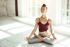 Pretty young girl meditating in the large room. Meditation and tranquility. Good looking nice calm woman sitting on the floor cross legged and closing her eyes Stock Images
