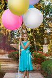 Pretty young girl with big colorful balloons walking in the park near the town - image stock images